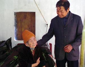 Đồng chí Lâm Văn Thứ, Trưởng Ban đại diện Hội NCT huyện Cao Phong thăm hỏi động viên bà Nguyễn Thị Tơ, hội viên NCT cô đơn chi hội TK 8, TT Cao Phong.